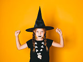 istock young halloween witch on orange background with black hat 1045448854