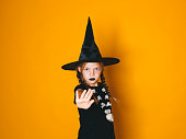 istock young halloween witch on orange background with black hat 1045448866