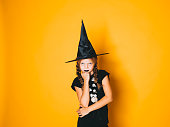 istock young halloween witch on orange background with black hat 1045448874