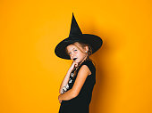 istock young halloween witch on orange background with black hat 1045449016