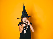 istock young halloween witch on orange background with black hat 1045449022