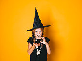 istock young halloween witch on orange background with black hat 1045449072