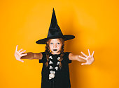 istock young halloween witch on orange background with black hat 1045449122