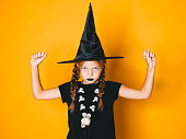 istock young halloween witch on orange background with black hat 1045449128