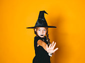 istock young halloween witch on orange background with black hat 1045449256