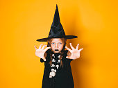 istock young halloween witch on orange background with black hat 1045450320