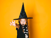 istock young halloween witch on orange background with black hat 1045451172