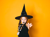 istock young halloween witch on orange background with black hat 1045451320