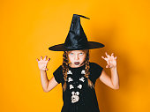 istock young halloween witch on orange background with black hat 1045451324