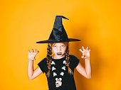 istock young halloween witch on orange background with black hat 1045451390