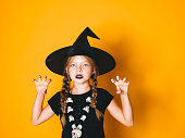 istock young halloween witch on orange background with black hat 1045453466
