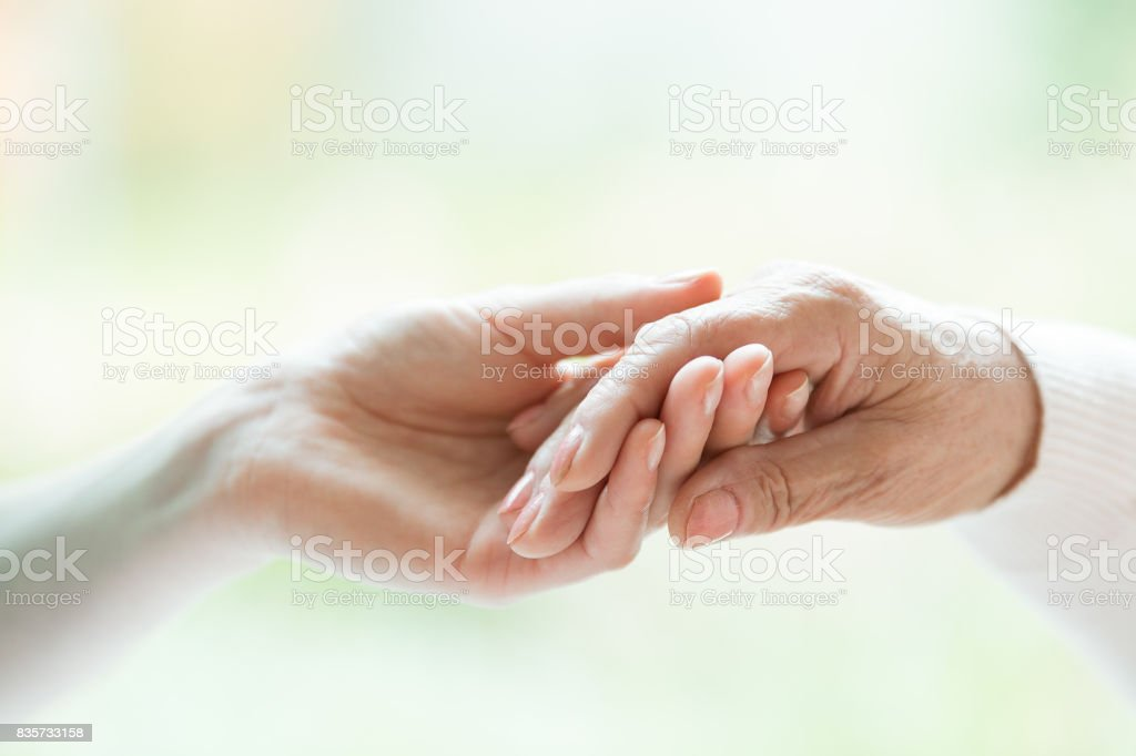 Young hand holding older one stock photo
