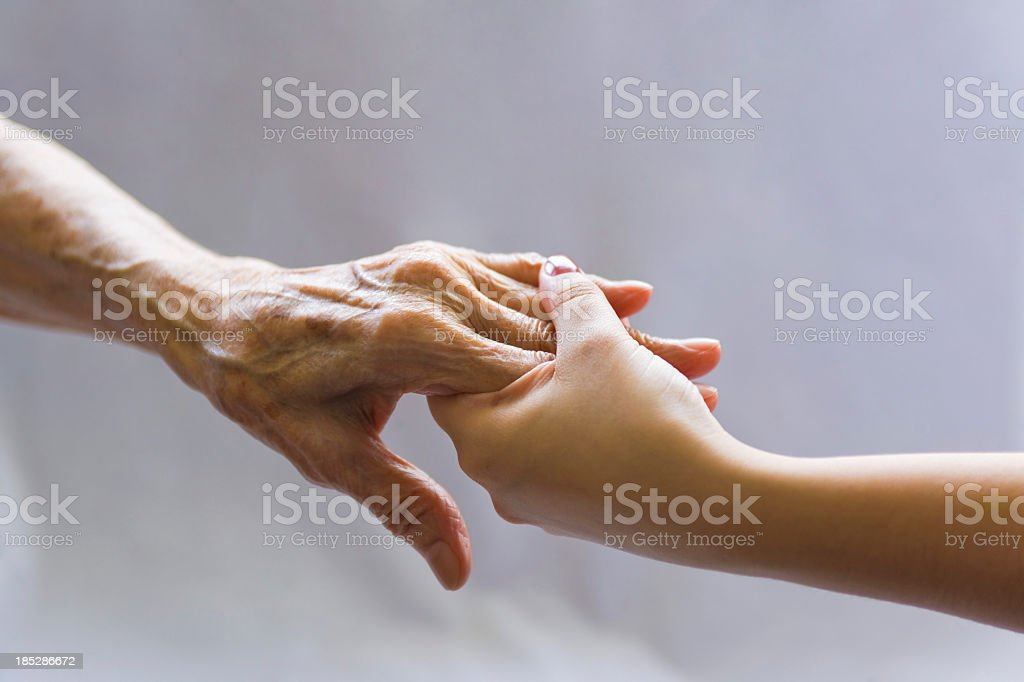 Young hand reaching out to a elderly persons hand stock photo