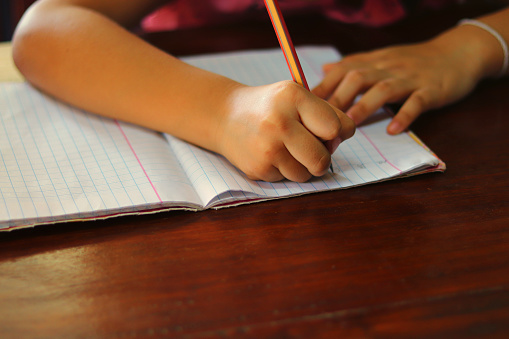 Young hand writing a lesson with a pencil on a book on wooden table - educational concept