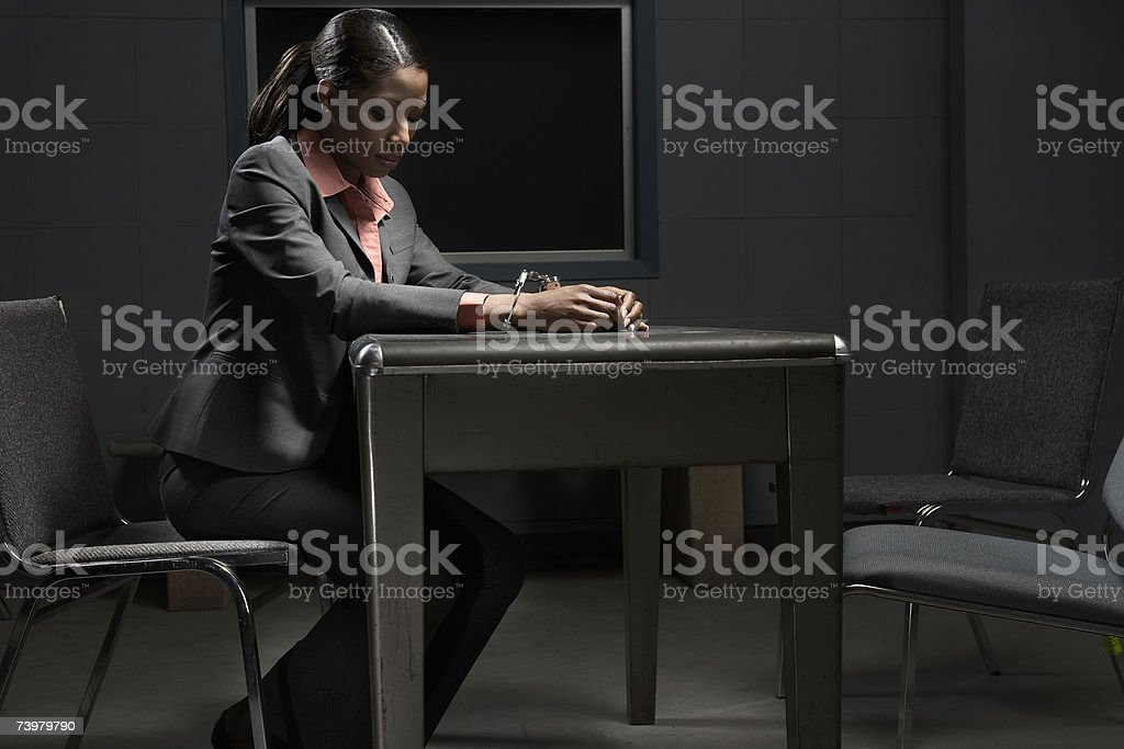 Young handcuffed woman sitting at table in interrogation room, side view stock photo