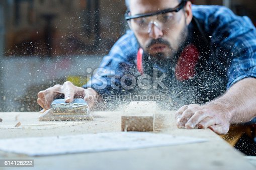 istock Young handosme carpenter blowing off sawdust 614128222