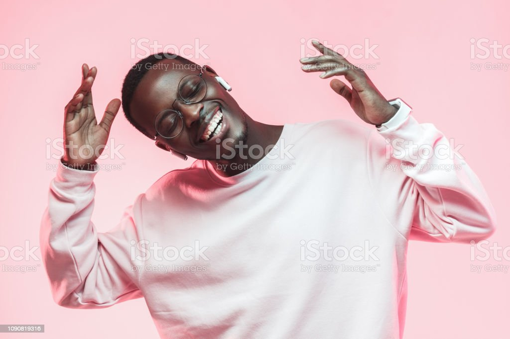 Young handsome african american man dancing, singing his favorite song with closed eyes, isolated on pink background royalty-free stock photo