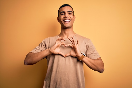 Young handsome african american man wearing casual t-shirt standing over yellow background smiling in love doing heart symbol shape with hands. Romantic concept.