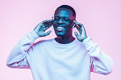 istock Young handsome african american man, wireless headphones and listening to his favourite song, dancing, smiling with closed eyes 1090819306