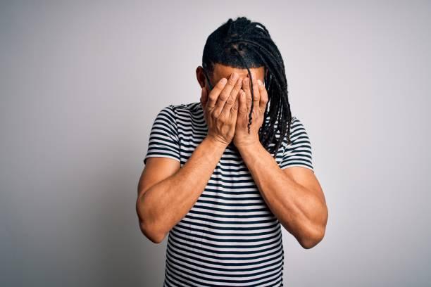 joven hombre afroamericano guapo con rastas con camiseta a rayas y gafas con triste expresión cubriendo la cara con las manos mientras llora. concepto de depresión. - vergüenza fotografías e imágenes de stock