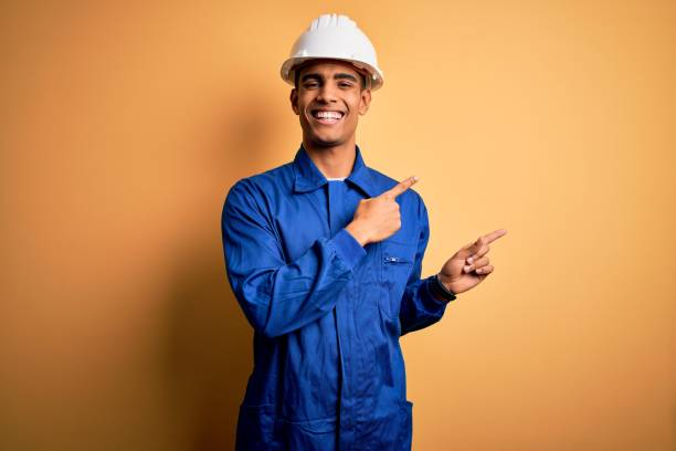 Young handsome african american worker man wearing blue uniform and security helmet smiling and looking at the camera pointing with two hands and fingers to the side. stock photo