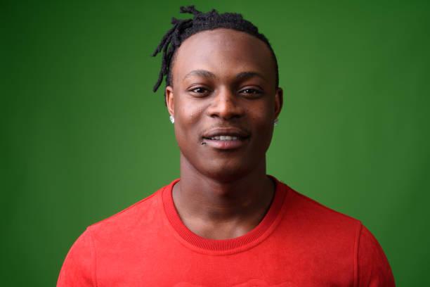 schönen jungen afrikanischen mann aus kenia vor grünem hintergrund - rote dreads stock-fotos und bilder