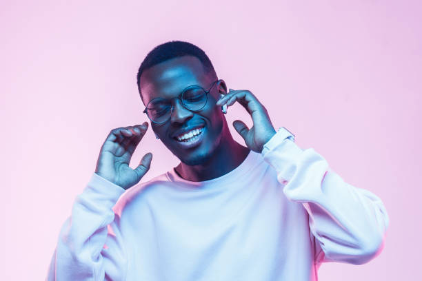 young handsome african man in wireless headphones and listening to his favourite song, dancing, smiling with closed eyes - music foto e immagini stock