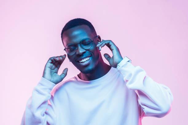 年輕英俊的非洲男子在無線耳機和聽他最喜歡的歌曲, 跳舞, 閉著眼睛微笑 - 霓虹色 個照片及圖片檔