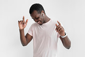 istock Young handsome african man in wireless headphones and natural pink t shirt listening to his favourite song, dancing, smiling with closed eyes 1009362336