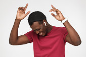 istock Young handsome african man in wireless headphones and red t shirt listening to his favourite song, dancing, smiling with closed eyes 1000217222