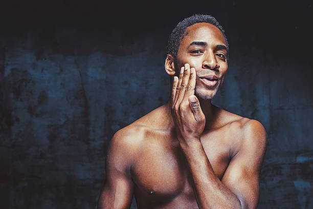 young handsome african-american man head and shoulders shot of young shirtless man over dark background. He is applying a cream on his face. shirtless male models stock pictures, royalty-free photos & images