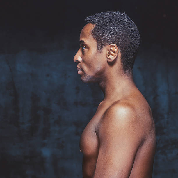 young handsome african-american man head and shoulders shot of young shirtless man over dark background, side view. shirtless male models stock pictures, royalty-free photos & images