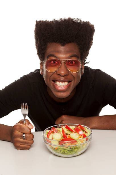 young handsome afro american guy eat salad isolated on white background. healthy food concept - foodie stock photos and pictures