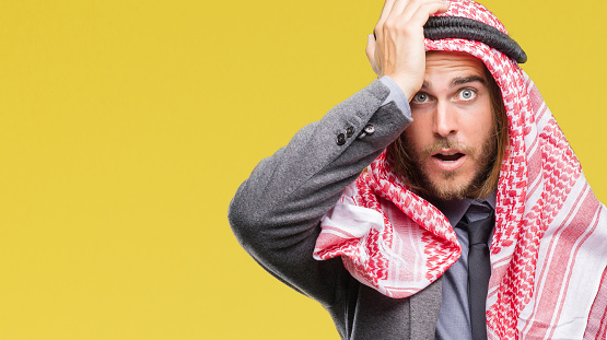 1046559700 istock photo Young handsome arabian man with long hair wearing keffiyeh over isolated background surprised with hand on head for mistake, remember error. Forgot, bad memory concept. 1124391721