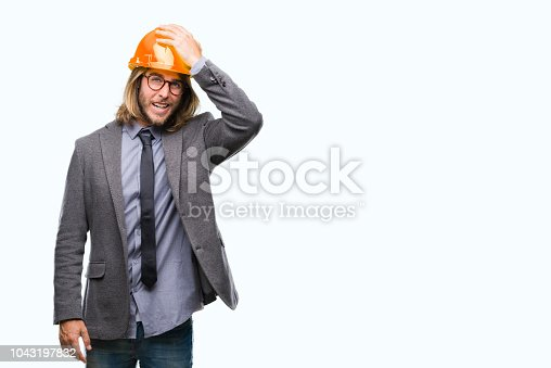 1046559700istockphoto Young handsome architec man with long hair wearing safety helmet over isolated background surprised with hand on head for mistake, remember error. Forgot, bad memory concept. 1043197832