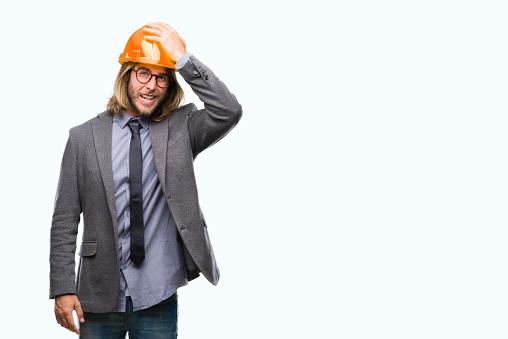 1046559700 istock photo Young handsome architec man with long hair wearing safety helmet over isolated background surprised with hand on head for mistake, remember error. Forgot, bad memory concept. 1043197832