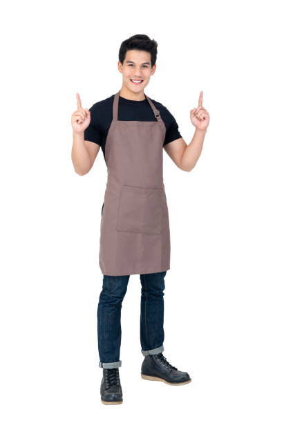 Young handsome Asian barista pointing up in studio white background stock photo
