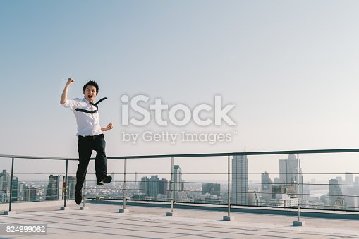 istock Young handsome Asian businessman jumping high, celebrate success winning pose on building rooftop. Work, job, or successful business concept. Cityscape background with copy space on sunny blue sky 824999062