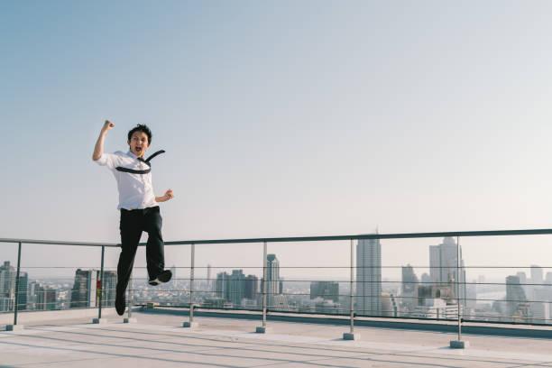 ジャンプ高い、若いハンサムなアジア系のビジネスマンは、建物の屋上に成功勝利ポーズを祝います。仕事、仕事、または巧妙なビジネス概念。晴れた青空にコピー スペースと都市景観の背景 ストックフォト