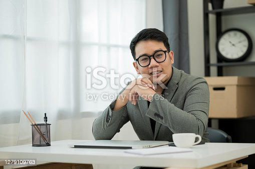Young handsome asian Ceo manager businessman middle-aged man around the age of 35 sitting in office near windows holding hands looking at camera and smile.