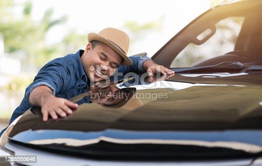 istock Young handsome asian man getting the new car. He hugged his car and was very happy. Buy or rent car concept. 1288555646
