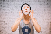 Young handsome Asian man having skincare facial mask on his face at home - cosmetology concept
