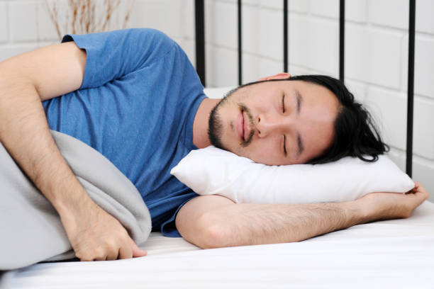 Young handsome asian man sleeping on white pill in bed, people lifestyle stock photo