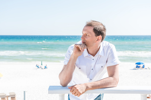 Young handsome attractive man serious on beach during sunny day in Seaside, Florida panhandle town village with ocean, hand on chin, leaning on railing, white shirt