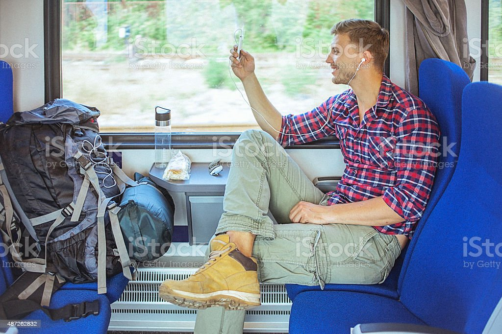 Young handsome backpacker in train, using smart phone stock photo