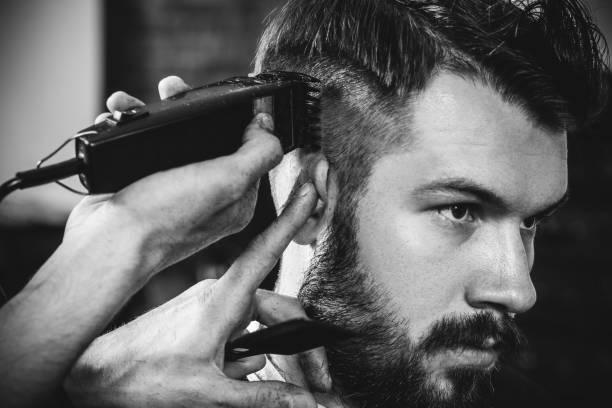 jeune beau barbier faisant la coupe de cheveux pour l'homme attirant dans le barbier - couper les cheveux photos et images de collection