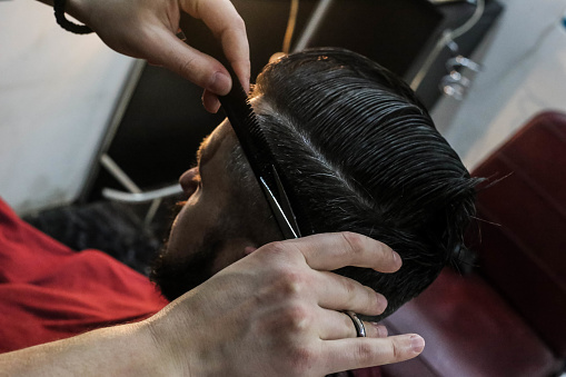 986804130 istock photo Young handsome barber making haircut of attractive man in barbershop 950398380