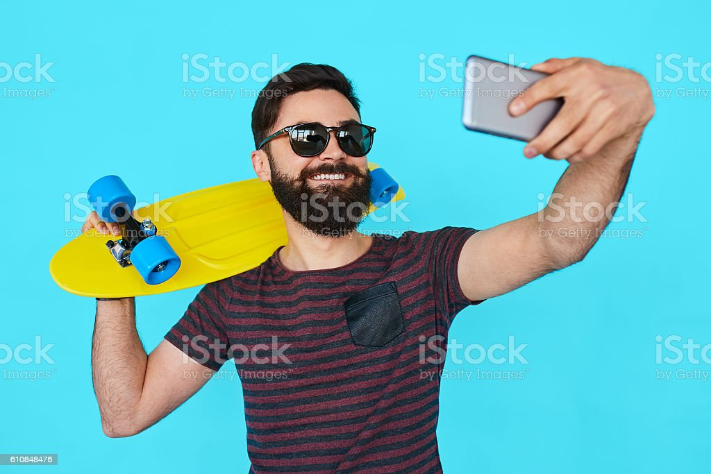 young handsome bearded hipster man makes selfie stock photo