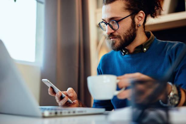 Junge hübsche bärtige Hipster sitzen in seinem Home-Office, halten Tasse Kaffee und mit Smartphone. – Foto