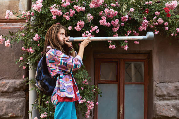 young handsome bearded man hippie with dreadlocks playing pipe of the pink roses background - didgeridoo stock photos and pictures